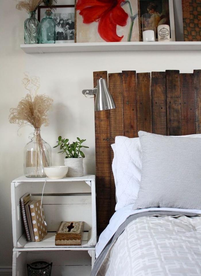 caisse de bois deco superposées de couelur blanche pour ranger livres et objets de decoration, tete de lit en palette, linge de lit gris et blanc