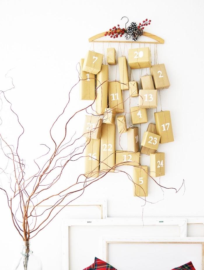exemple de calendrier de l avent original en petits cadeaux emballés suspendus sur un cintre en vois décoré pommes de pin et houx