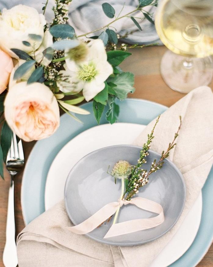 plier une serviette en forme de triangle avec assiettes et décoration florale, composition florale décorative fleurs champetre
