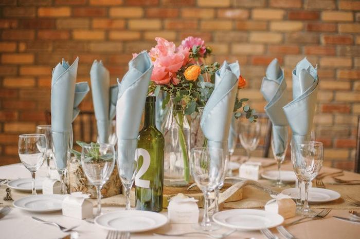 serviettes en tissu grises dans des verres à vin, nappe blanches, assiettes blanches et centre de table bouquet de fleurs dans une bouteille en verre recyclée, numéro de table écrit sur bouteille
