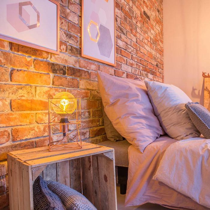 table en cagette bois brut avec des coussins rangés à l intérieur et une lampe ampoule dessus, mur de briques, linge de lit gris