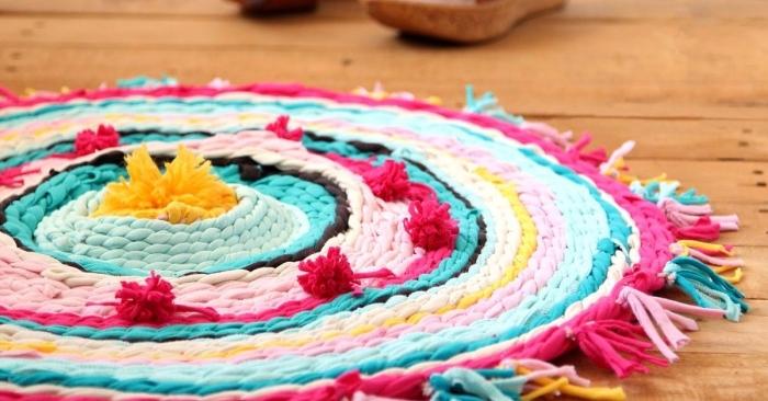 modèle de tapis rond tressé en bandes de tissu coloré avec décoration en tassels et pompons, activité manuelle ado facile