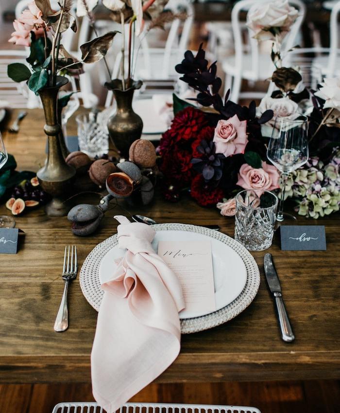 couverts de table noués autour d une serviette en tissu rose dans assiette, composition florale en guise de centre de table de bois brut