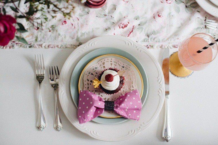 deco table mariage originale avec pliage de serviette en papier en forme de noeud de papillon rose, cupcake dans assiettes chemin de table en tissu floral