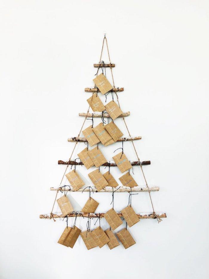 calendrier de l avent en branches de bois flotté et fil sur un mur blanc avec de petits paquets emballage cadeau original en papier journal vintage