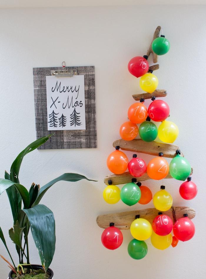 sapin de noel original en bois flotté et des ballons numérotés et colorés sur le fond d un mur blanc, calendrier de l avent original