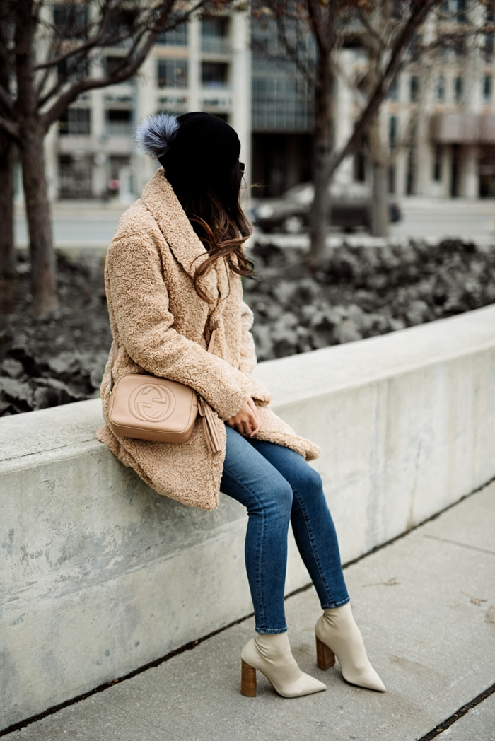 manteau teddy bear beige, petit sac beige, jeans bleus, femme assise, manteau long fourrure synthétique