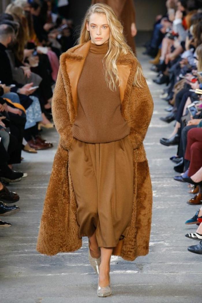 un modèle qui présente un manteau teddy bear, blouse chocolat, pantalon cognac ample