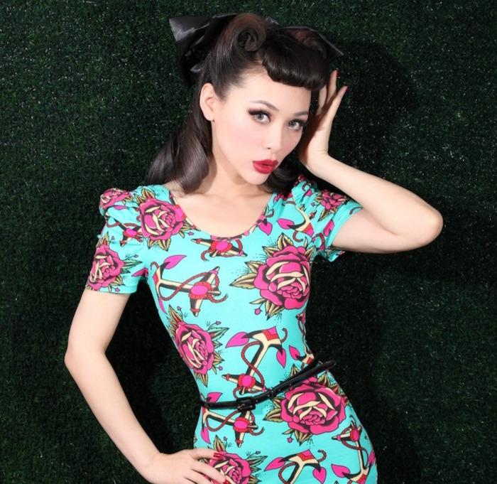 modele pin up moderne avec coiffure retro victory rolls et robe coupe vintage années 50 et maquillage pinup eye liner