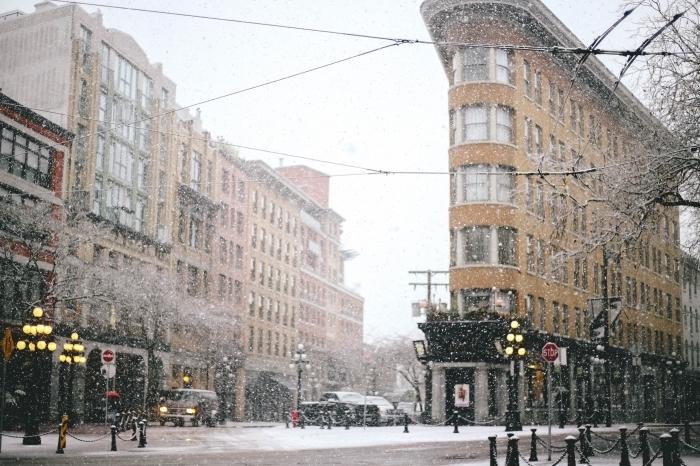 image de noel gratuite a telecharger, photo de la neige qui tombe dans une ville en hiver aux lumières allumées