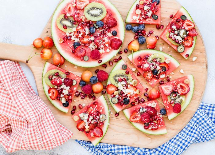 dessert ou apero enfant anniversaire, tranches de pastèque aux fruits et noix sur une planche à découper