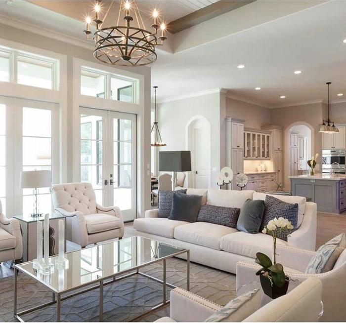 salon clair, chandelier rustique, portes fenêtres, tapis gris, sofas blancs, coussins gris, cuisine ilot central gris et blanc