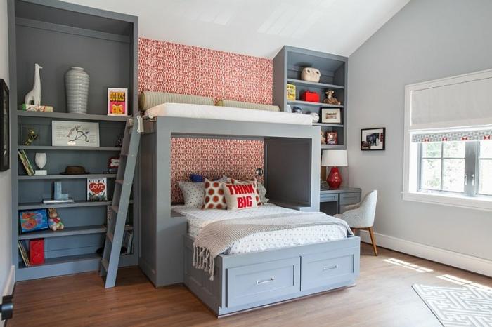 lit enfant de deux personnes, bibliothèques grises, papier peint rouge, petit bureau gris, sol en bois