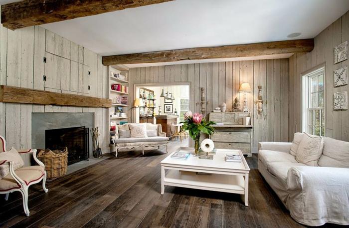 sol en bois, table de salon blanche, chaise ancienne avec coussin de lin, cheminée et lambris mural bois