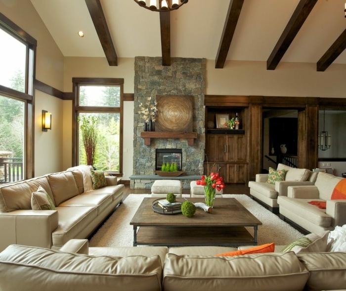 table basse en bois, sofas beiges, bouquet de fleurs rouges, manteau de cheminée pierre, poutres apparentes
