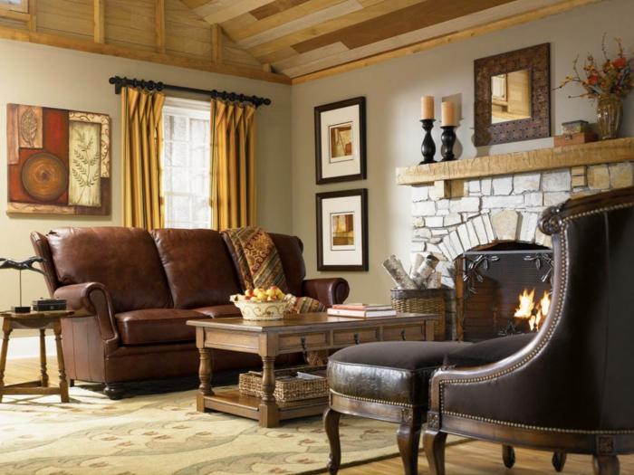 tapis beige, table basse en bois, fauteuils en cuir, rideaux jaunes, cheminée parement pierres, peintures encadrées