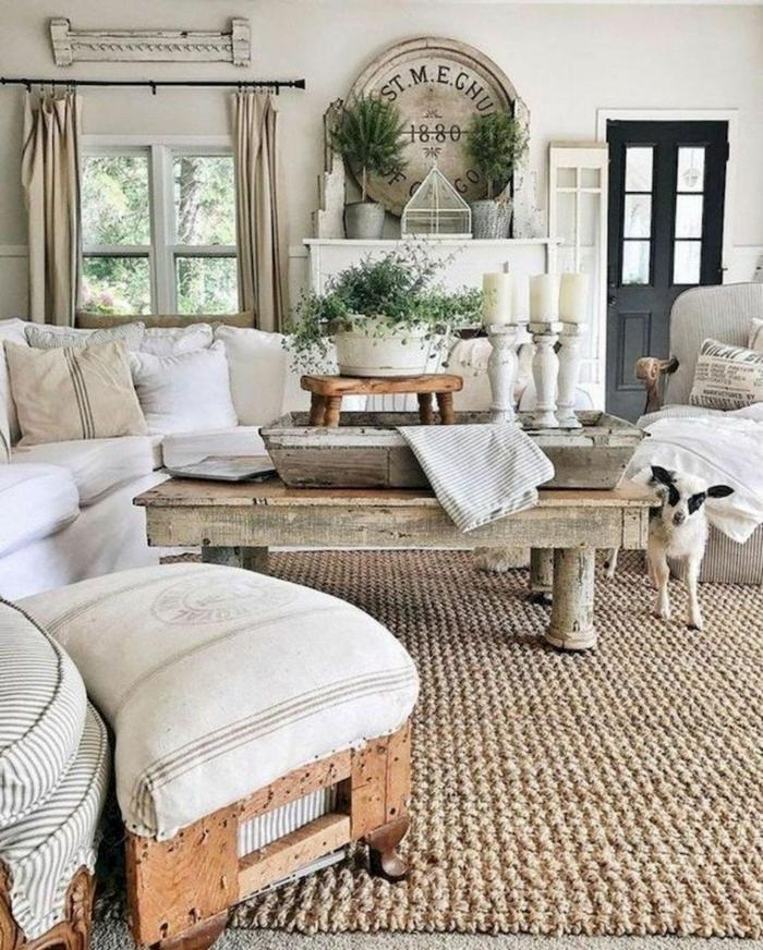 deco maison de campagne cosy, tapis de jute, tabouret de palette tapissé, grande table esprit brocante, grands bougeoirs blancs, petit agneau blanc et noir