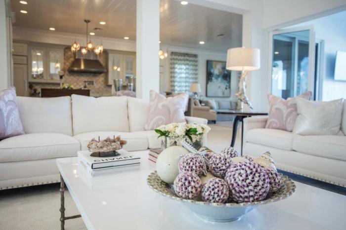table basse blanche, assiette pleine d'objets décoratifs, sofas blancs, lampe en bois flotté, salle de séjour blanche