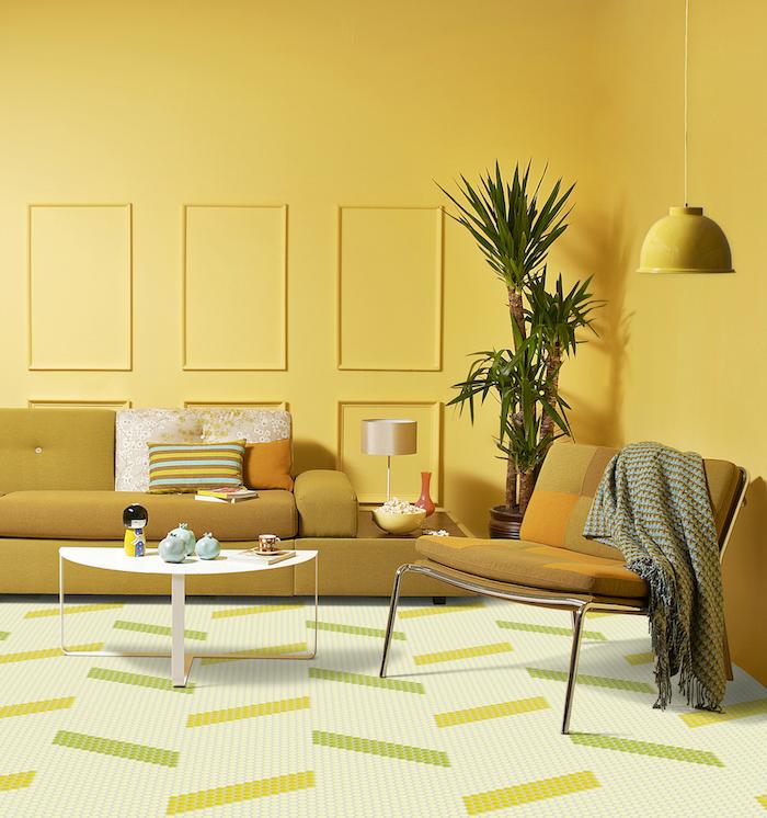 deco salon jaune avec un canapé jaune moutarde et chaise jaune, table minimaliste blanche, palmier interieur en pot