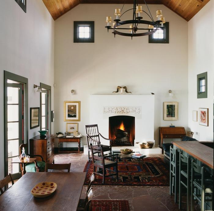 deco maison de campagne cosy, table en bois foncé, sol en pierre rouge, chandelier noir, rénovation d'ancienne grange, grande cheminée blanche