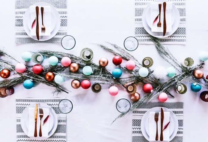 décoration de noel avec guirlande en boules colorées et branches de sapin, exemple pliage de serviette facile