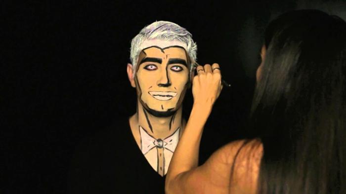 maquillage style pop art pour homme, cheveux blancs, contours des yeux noirs, lentilles couleur néon, costume et papillon peint sur le cou