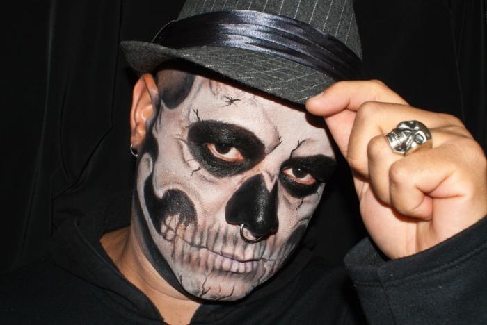 maquillage halloween squelette, bague tête de mort, chapeau cylindre, dents et structure du crâne apparente