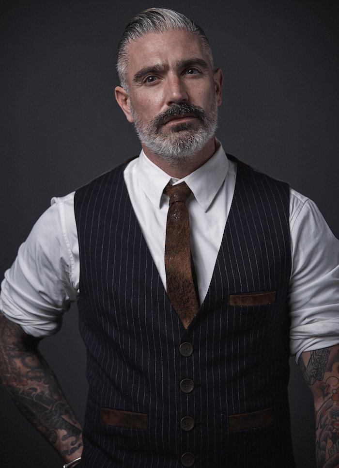 homme hipster avec barbe grise et coupe pompadour poivre et sel et gilet de costume rayé sur chemise blanche et cravate cuir marron vieillit retro