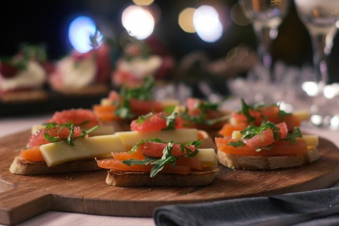 plat de service en bois, tartines au saumon et au fromage, amuse bouche apéritif facile sur la table de fête