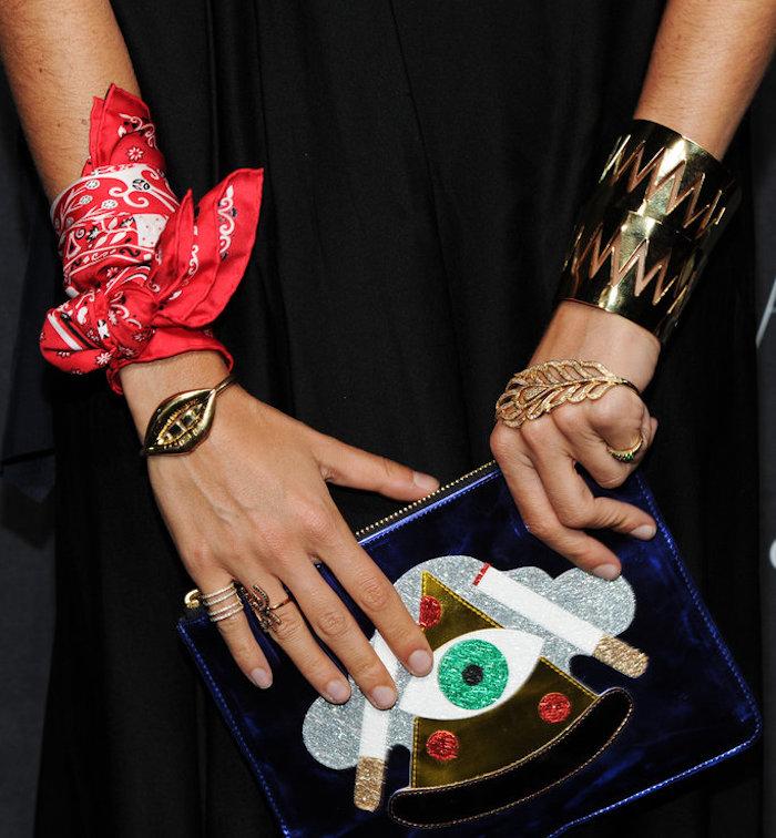 avant bras et mains de femme avec accessoires et bijoux dont un foulard rouge attaché au poignet comme un bracelet