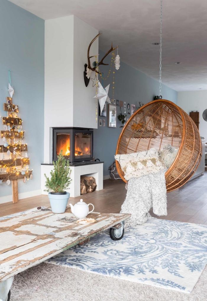déco cocooning salon scandinave en blanc et bleu gris qui invite à la détente grâce à sa chaise suspendue en rotin et la décoration de noêl et son sapin de noël en bois décoré de petites guirlandes lumineuses