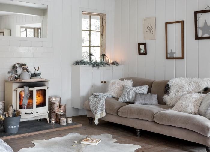 déco salon scandinave traditionnelle dans l'esprit de fête nordique avec un canapé moelleux recouvert de coussins cosy et d'un plaid en fausse fourrure, coin cheminée rustique chic