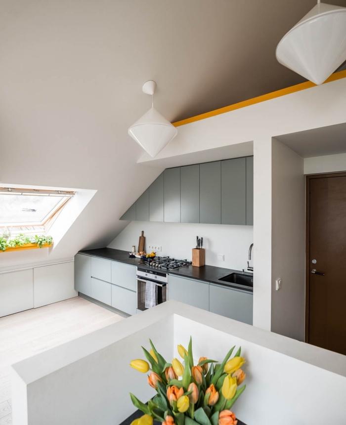 cuisine en blanc et gris avec plan de travail noir, exemple de cuisine sous pente, agencement cuisine en longueur