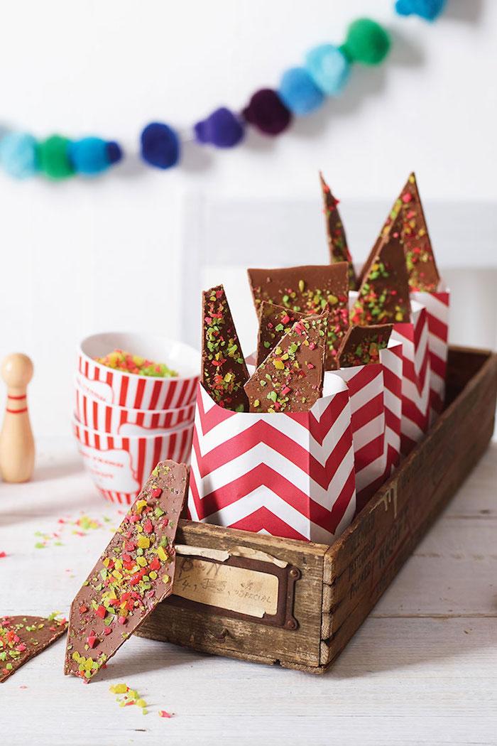 sac en papier rempli de chocolat maison décoré de pistaches et bonbons, surprise enfant anniversaire, cadeau anniversaire enfant