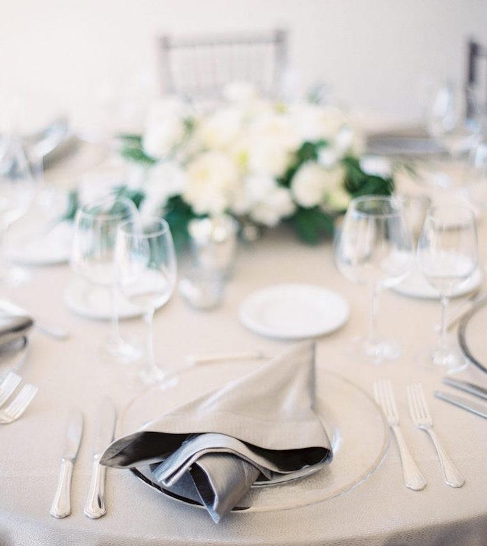pliage de serviette facile et nonchalant avec serviette grise dans assiette blanche, couverts de table élégants, pièce centrale décorative en fleurs blanches