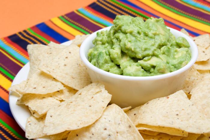 menu mexicain guacamole et doritos chips, dans une assiette blanche, idée repas simple à partager pour anniversaire