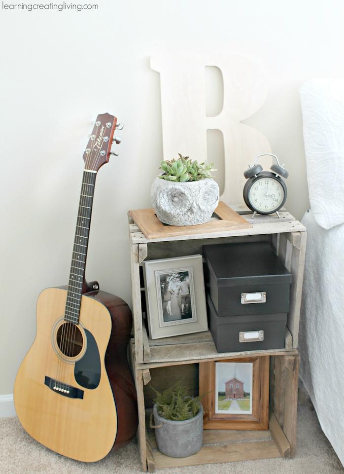 caisses de bois superposées style rustique brut, rangement plantes, decorations, objets vintage, guitare, linge de lit blanc