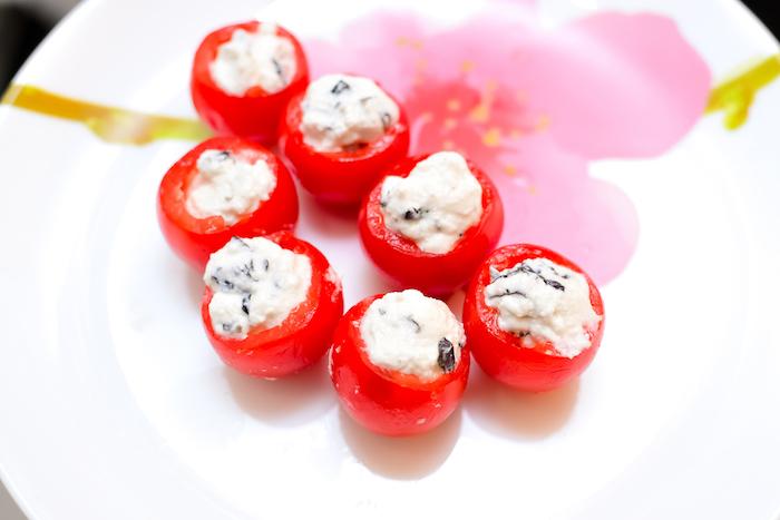 tomate cerise farci de fromage à la crème ricotta et olives dans une assiette à motif fleuri, idée repas équilibré anniversaire
