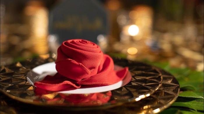 modèle pliage de serviette pour noël stylé, faire une rose en tissu rouge pour déco table de fête, idée serviette en forme florale