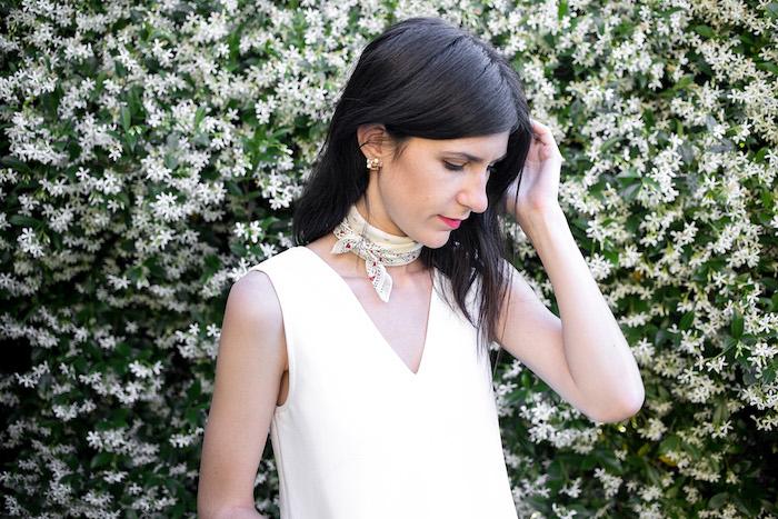 femme brune avec foulard beige attaché autour du cou comme accessoire mode et haut blanc