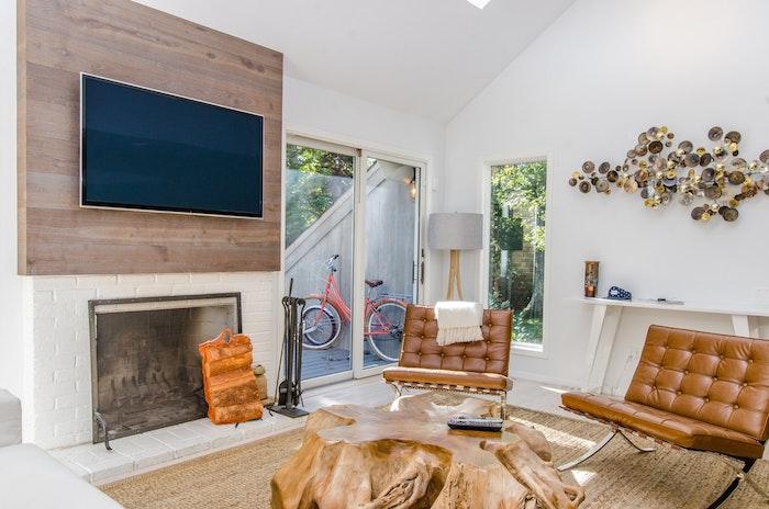 choisir sa télévision écran plat au dessus d'une cheminée, tapis beige, chaises en cuir, table en tronc d arbre, tv en hauteur
