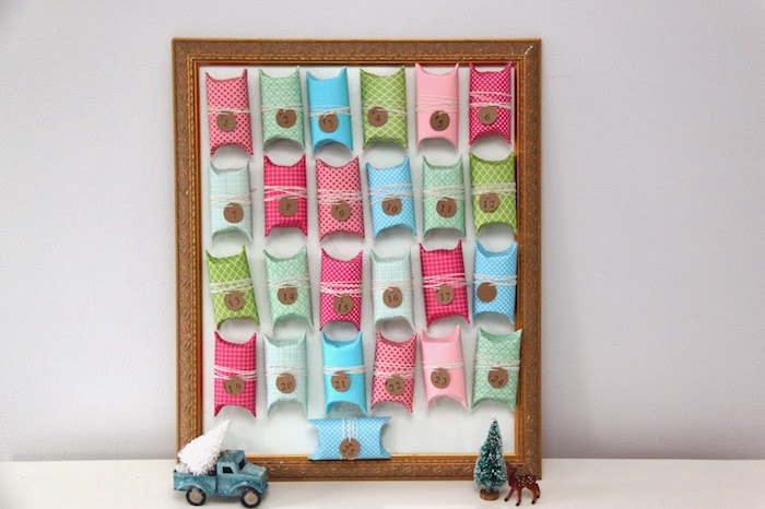 exemple de cadre bois avec des rouleaux de papier toilette colorés boîte cadeau surprise sur fond blanc, calendrier d el avent maison