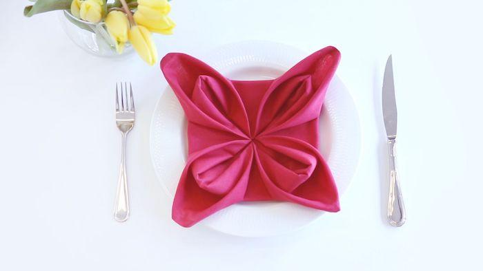 fleur de lotus en serviette couleur framboise dans assiette blanche, couverts de table argent, deco florale en tulipes jaunes