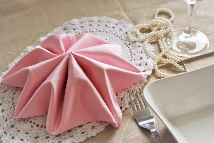 comment plier une serviette tissu rose en forme d étoile sur napperon blanc, deco mariage collier de perles, couverts et vaisselle simple