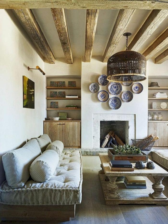 idée déco salon style rustique, grand matelas gris avec grands coussins, poutres bruts au plafond, grand chandelier rustique
