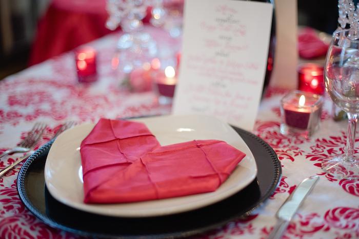 décoration romantique de table avec nappe blanche à motifs fleuris rouges, serviette en forme de coeur rouge, deco bougies miniatures