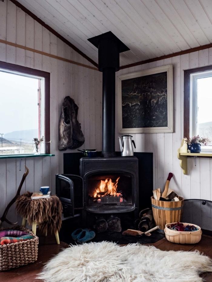 une image cocooning représentant l'intérieur d'un chalet avec un coin hygge aménagé près de la cheminée