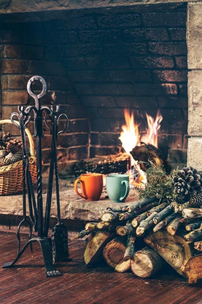 image cocooning d'un coin cheminée traditionnel avec un panier déco en rotin plein de pommes de pin
