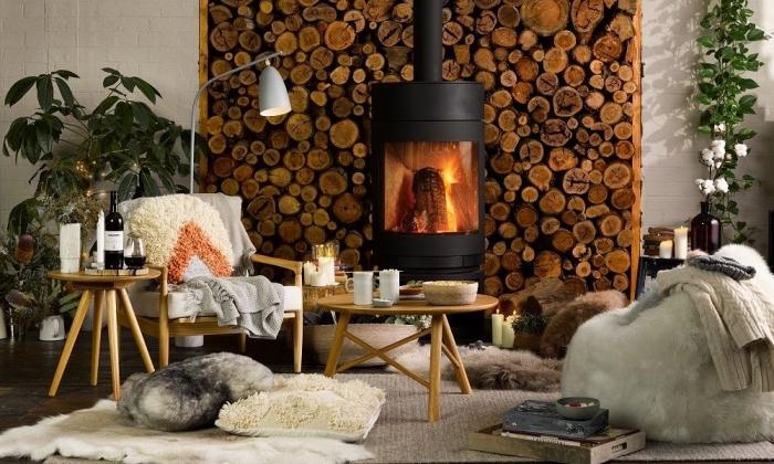 coin cheminée cocoonisé avec des matières douces et accents déco naturels, coin hygge deco d'esprit scandinave avec des coussins jetés au sol, un pouf douillet