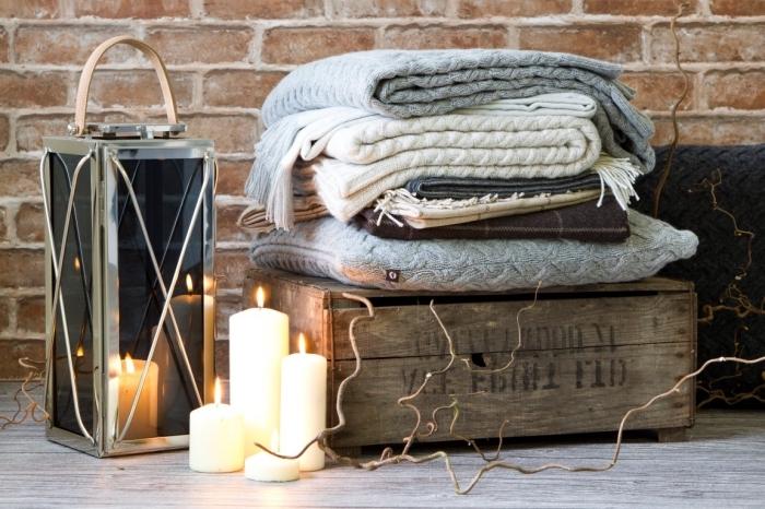 image cocooning avec une pile de plaids douillets sur une caisse en bois vintage, une lanterne déco et quelques bougies allumées